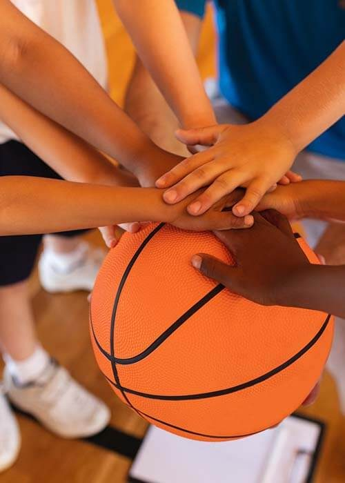 close-up-of-schoolkids-forming-hand-stack-on-basketball-at-basketball-court-in-school